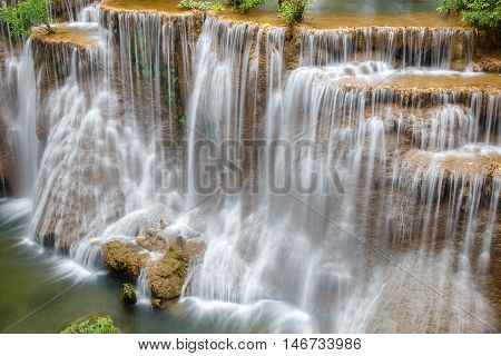 Water flowing over rocks in Huai Mae Khamin waterfall cascade in a forest.