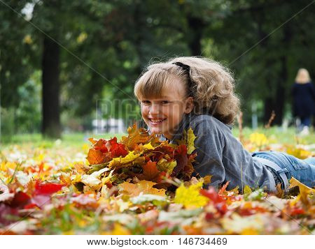Great beautiful girl lying amongst autumn leaves