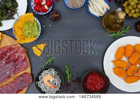 Table with spanish tapas - anchovies with peppers padron, jamon, croquetes, guacamole and olives, frame with copy space