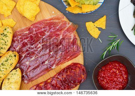 Table with spanish jamon and chorizo tapas, picnic table