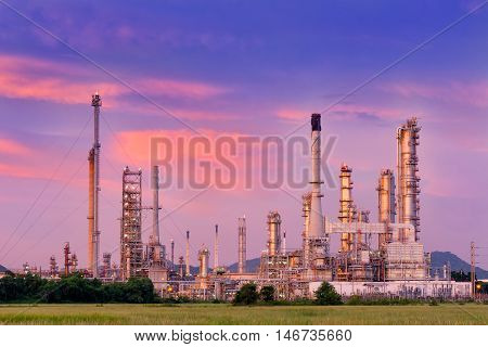 Twilight of oil refinery plant on cloudy background.