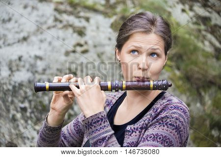 Young woman playing an indian wooden flute