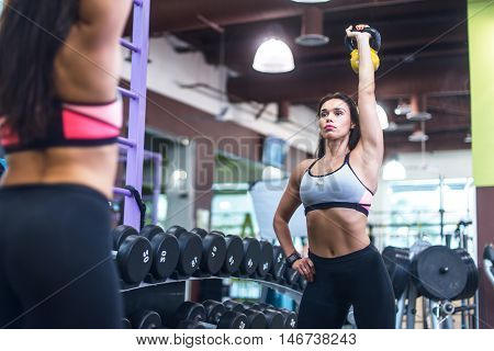 Portrait of fit woman looking at mirror, exercising with kettlebell in gym.