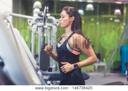 Fit woman exercising on treadmill in gym