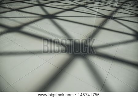 Shadow on the ceramic floor from steel structure roof ceiling made of metal and glass