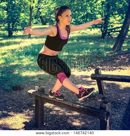 Young woman exercising in nature balancing on wooden hurdle