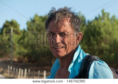 Portrait Of A Happy Attractive Handsome Senior Man Outside With Back Pack Smiling