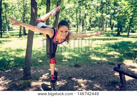 Balancing exercise - young woman exercising in park, color image