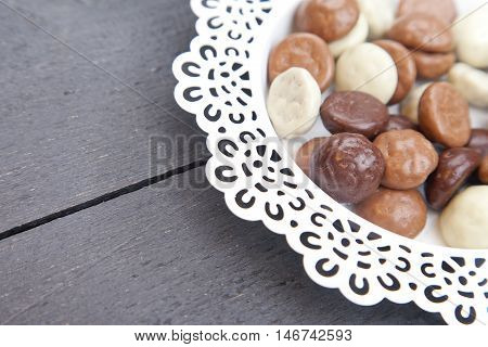 Dutch candy chocolate pepernoten on white plate on black wooden background