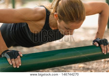 Female athlete doing push-ups, color image, close up