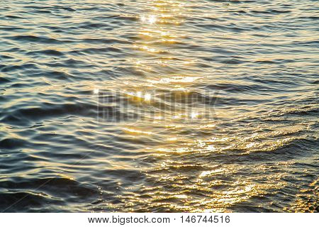 Blue sea water surface background at sunset with sparks