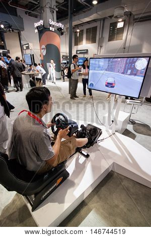 SHANGHAI CHINA - SEPTEMBER 2 2016: Attendee of Huawei Connect 2016 information technology conference test auto training simulator at exhibition hall in Shanghai China on September 2 2016.