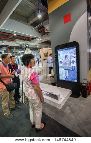 SHANGHAI CHINA - SEPTEMBER 2 2016: Attendees of Huawei Connect 2016 information technology conference test virtual fitting room simulator at exhibition hall in Shanghai China on September 2 2016.
