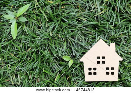 Wooden toy house on concept green background