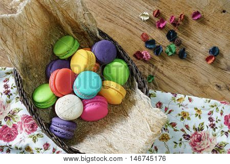 Sweet and colorful French macarons in rattan basket with dry flower