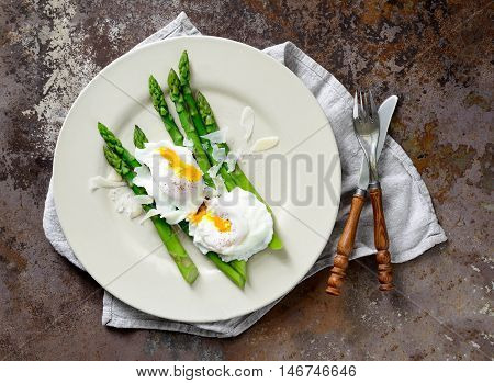 Asparagus with poached eggs seasoned with parmesan top view