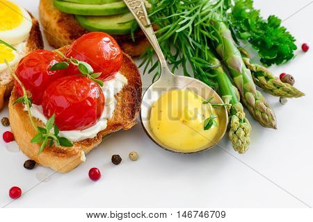 Holland sauce in a spoon with sandwiches and vegetables