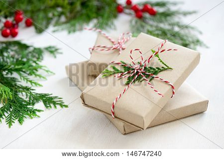 Xmas gifts wrapped in a natural coloured paper and decorated with a traditional Christmas twine and fir branches