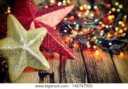 Chrismas decoration in shimmering lights on wooden weathered background stylized vintage photo