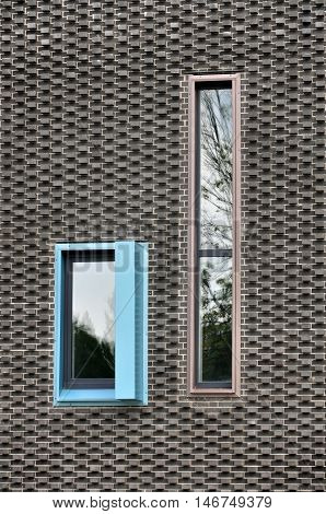 Modern patterned wall of black brick and with vertical colored windows.