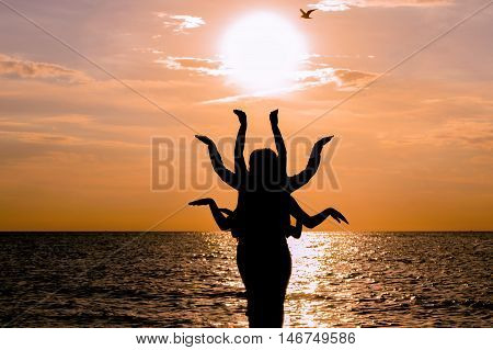 Indian dance silhouette on beautiful beach during sunset. Silhouette of human figure with many arms
