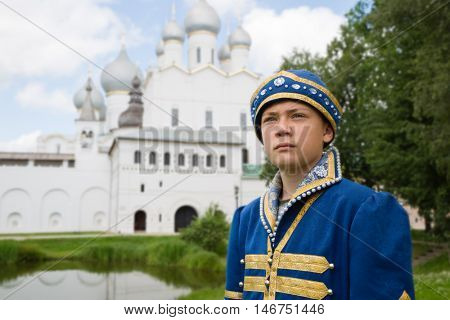 Boy in national russian suit Middle Ages on the background the Christian Cathedral in Kremlin Rostov Great (Veliky)