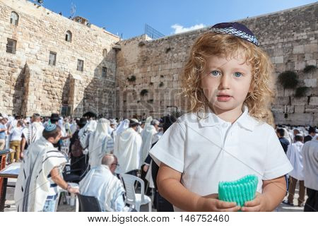 The Jewish holiday of Sukkot. Cute little boy with long blond curls and blue eyes in blue skullcap. He stands at Western Wall of Temple