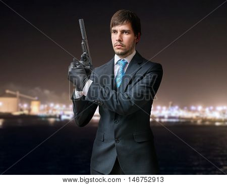Secret Agent Or Killer Holds Pistol With Silencer In Hands At Ni