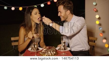 Loving young man feeding his girlfriend cake