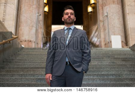 Portrait of a confident businessman walking down the stairs in an ancient building