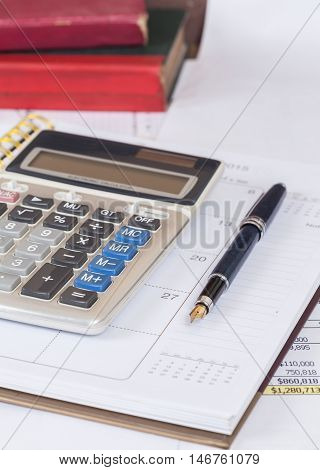 calculate and pen on calendar book on table