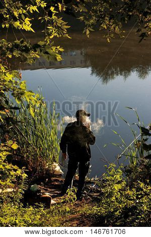 Smoking man. Fisherman stands on banks of river in early morning. Cloud of tobacco smoke. Beautiful summer landscape with water and trees