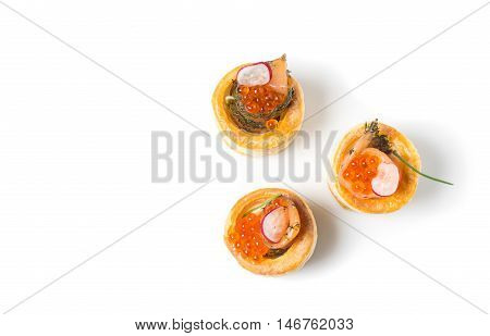 Delicious appetizers with graved salmon and golden caviar served in puff pastry towers isolated on white