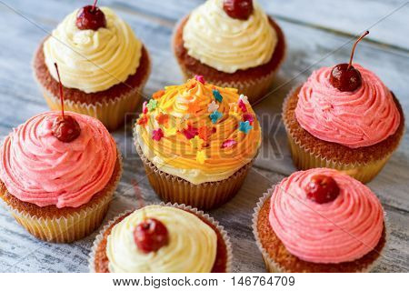 Cupcakes with frosting. Small colorful desserts. Easy recipe of tasty pastry. Soft dough and buttercream.