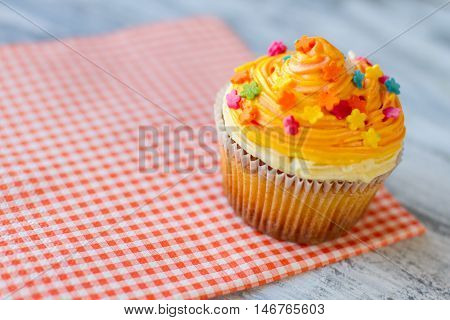 Cupcake on red napkin. Bright-colored icing. Choose best dessert at cafe. Tiny sugar flowers.
