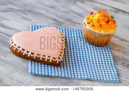 Orange cupcake and heart biscuit. Confectionery on blue napkin. Love is sense of life. Wonders in simple things.