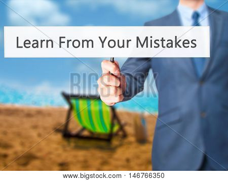 Learn From Your Mistakes - Businessman Hand Holding Sign