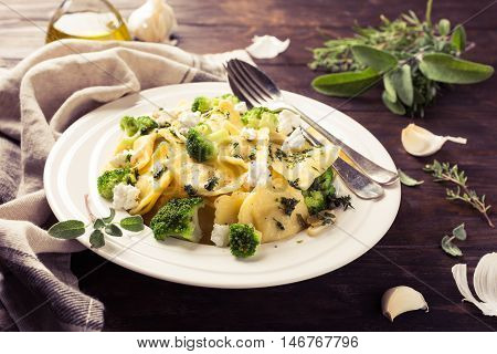 Italian ravioli with goat cheese, broccoli and herbs on old wooden background. Healthy food. Retro style toned