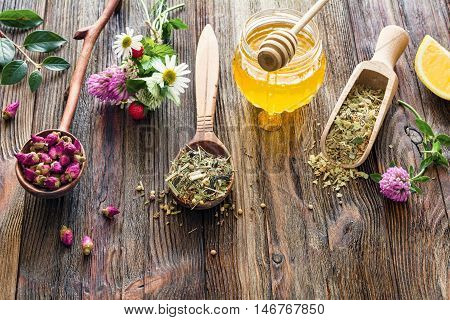 Assortment of dry herbal tea in wooden spoons, jar of honey, fresh flowers