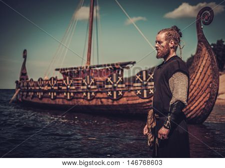 Serious viking warrior with sword standing near Drakkar on the seashore.