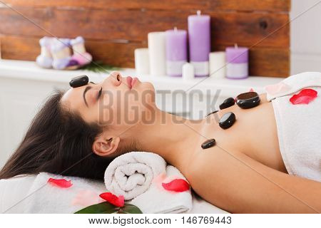 Black marble stone massage in ayurvedic spa. Beautiful girl in wellness center. Professional relaxation procedure to attractive young indian girl in beauty parlor.