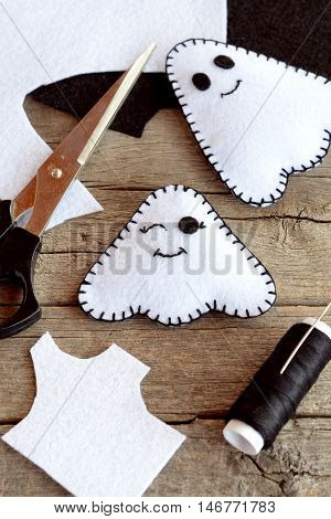 Cute white ghosts crafts, felt sheets, scissors, thread, needles on an old wooden background. Easy Halloween felt ghosts decor. Halloween sewing project for kids