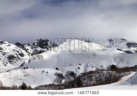 Ski Resort And Sunlight Mountains In Clouds