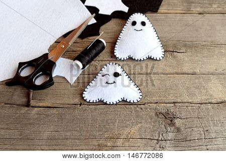 Hand made Halloween ghosts ornaments. Two little felt ghosts, felt scraps, scissors, thread, needle on an old wooden background. Cute Halloween characters. Top view