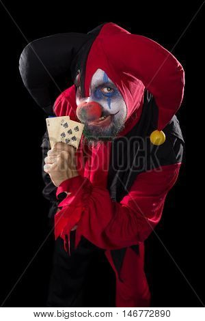 Red And Black Colored Jester Holding Playing Cards, Concept Poker And Gambling