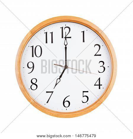 Big round clock shows exactly seven o'clock