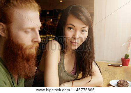 Interracial Couple Having Date At Cafe. Attractive Asian Girl With Happy Look Sitting Next To Her Re