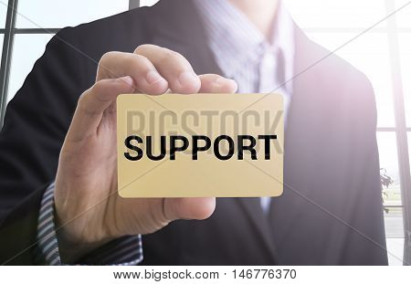 businessman hand holding a business card with a message support for advertise concept.