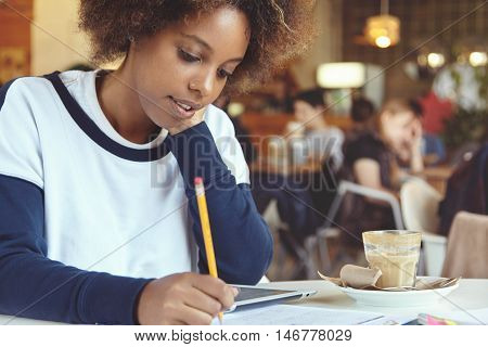 Beautiful African Graduate Student Girl Holding Pencil, Writing Down In Sheet Of Paper While Prepari