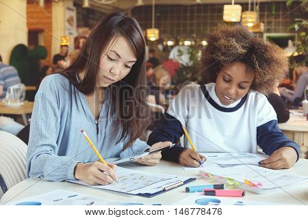Two female partners working on assignment sitting at table with notebooks and digital tablet writing down plans and ideas for their start up project. Asian girl holding touch pad and making notes